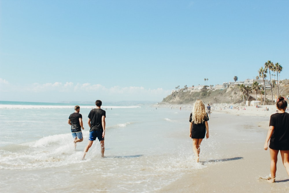 group of people walking on sand beside body of water during daytime