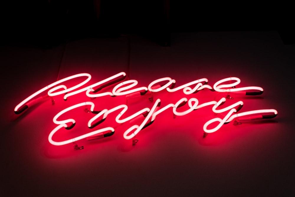 Please Enjoy neon signage is turned on