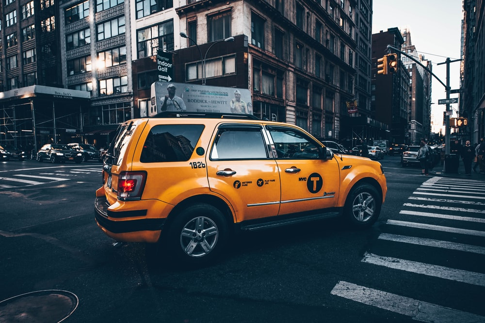 selective focus photo of yellow taxi SUV parked in between road surrounded by buildings