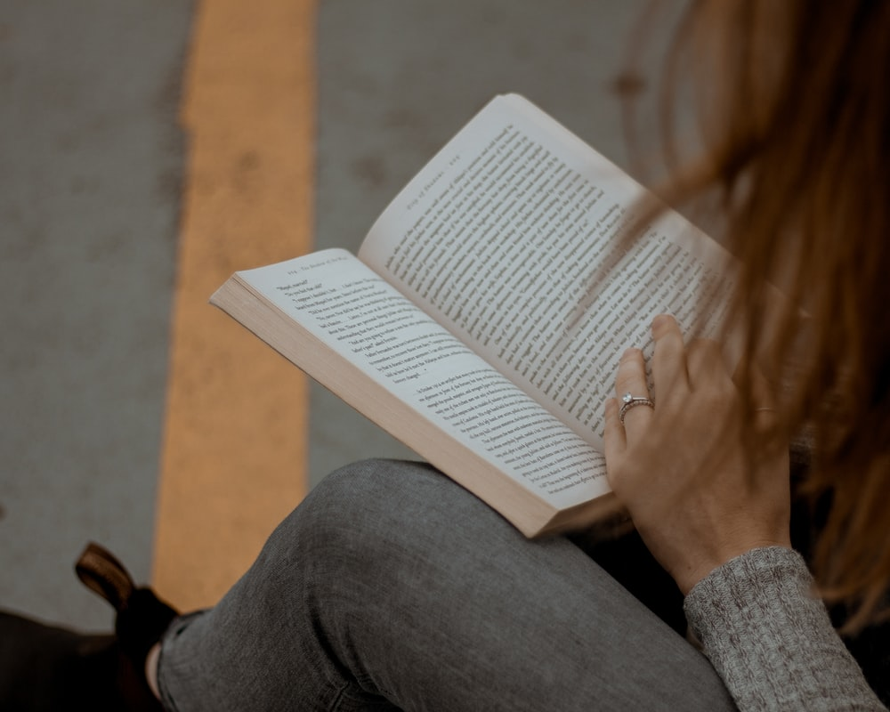 woman wearing gray long-sleeved shirt reading book