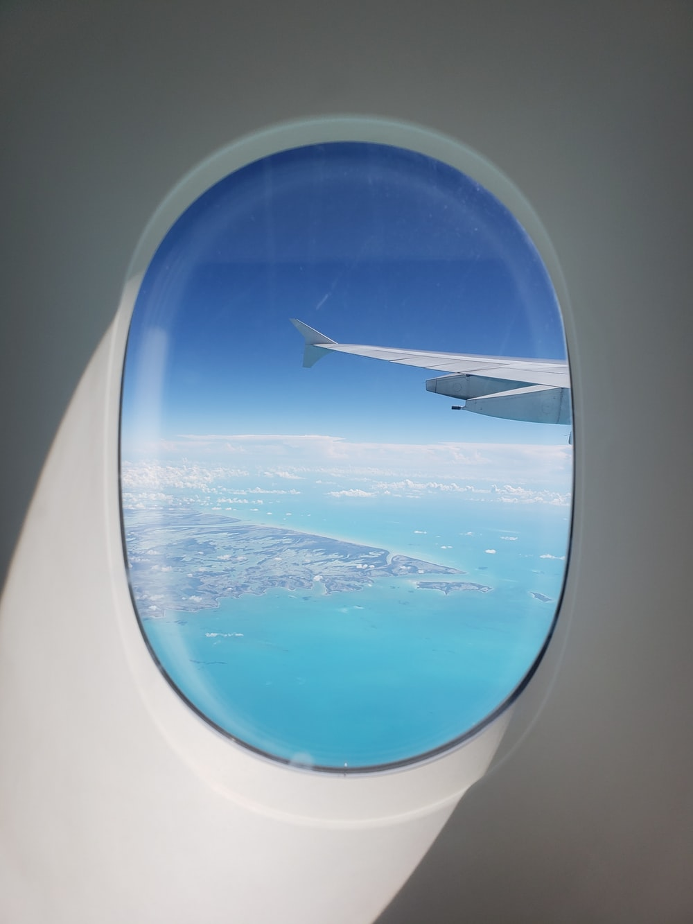 plane wing on air above body of water during daytime