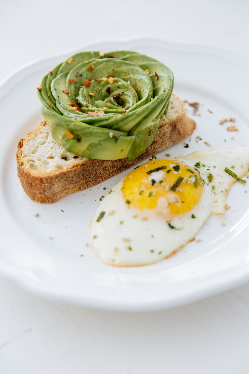 bread with sunny side-up egg on white plate
