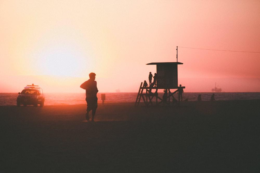 silhouette of person near car and beach