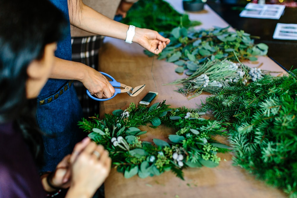 person holding scissors and leaf wreath