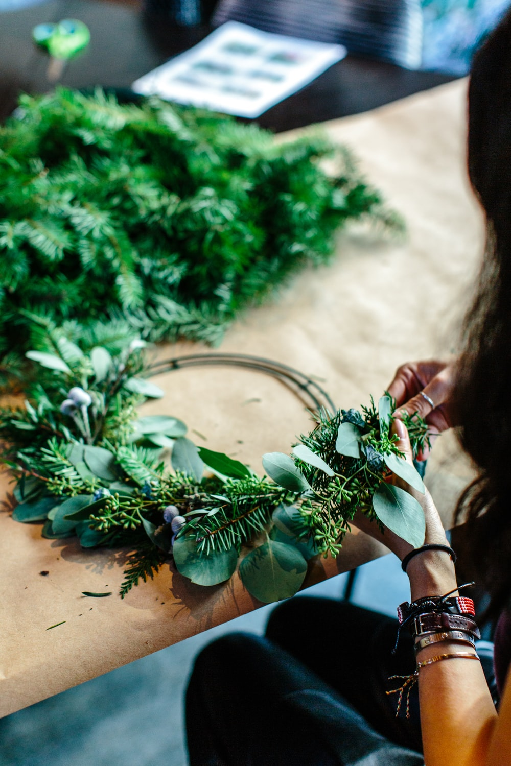 woman making green floral wreath on table