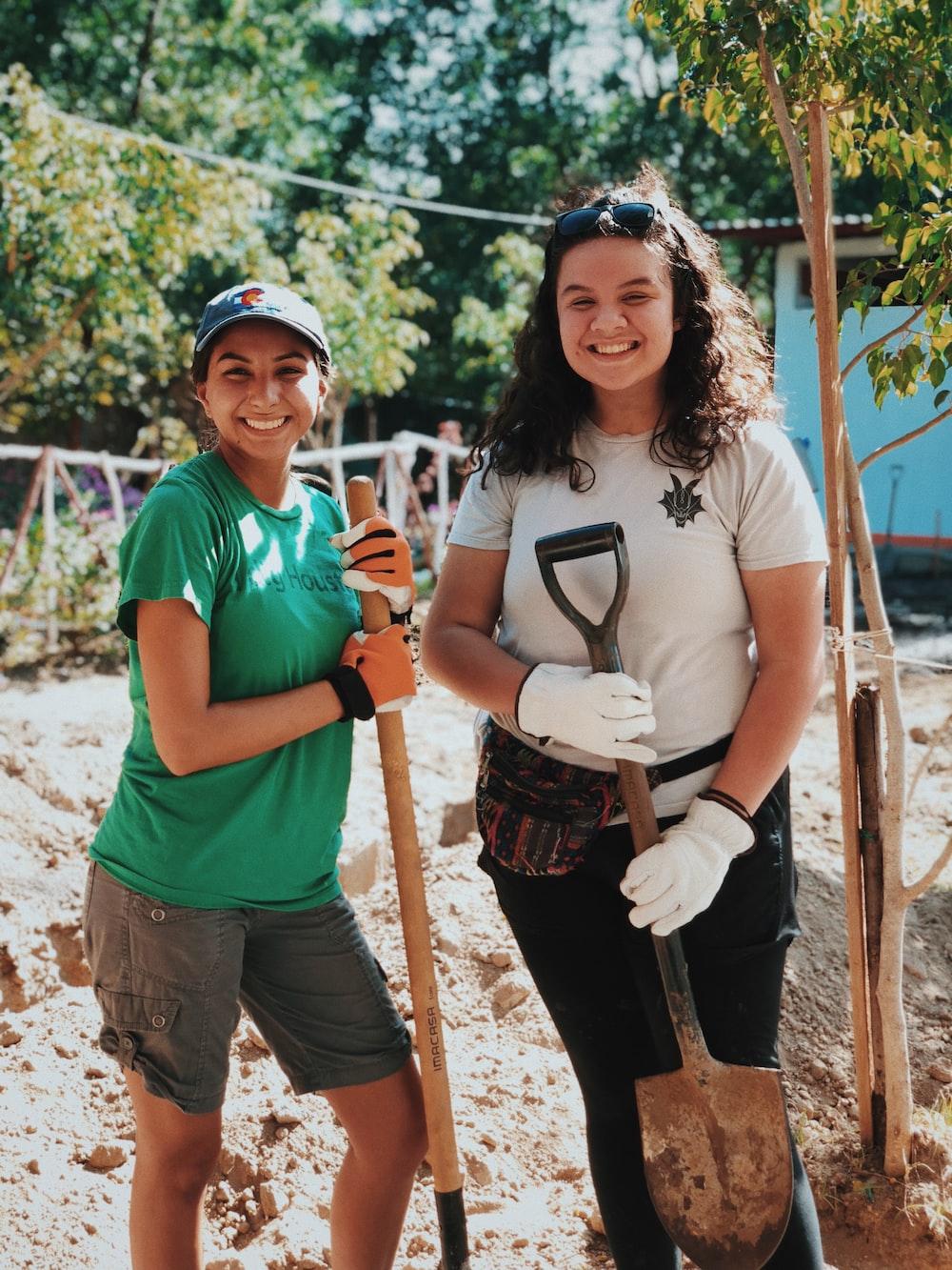 two women holding shovels