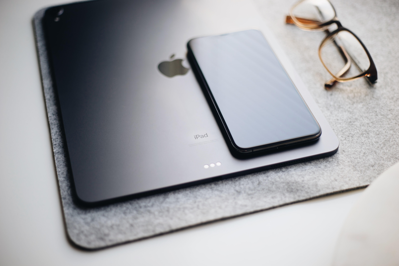 black iPad beside eyeglasses