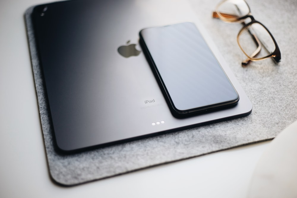 black iPad beside eyeglasses