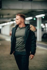 standing man wearing jacket and black pants