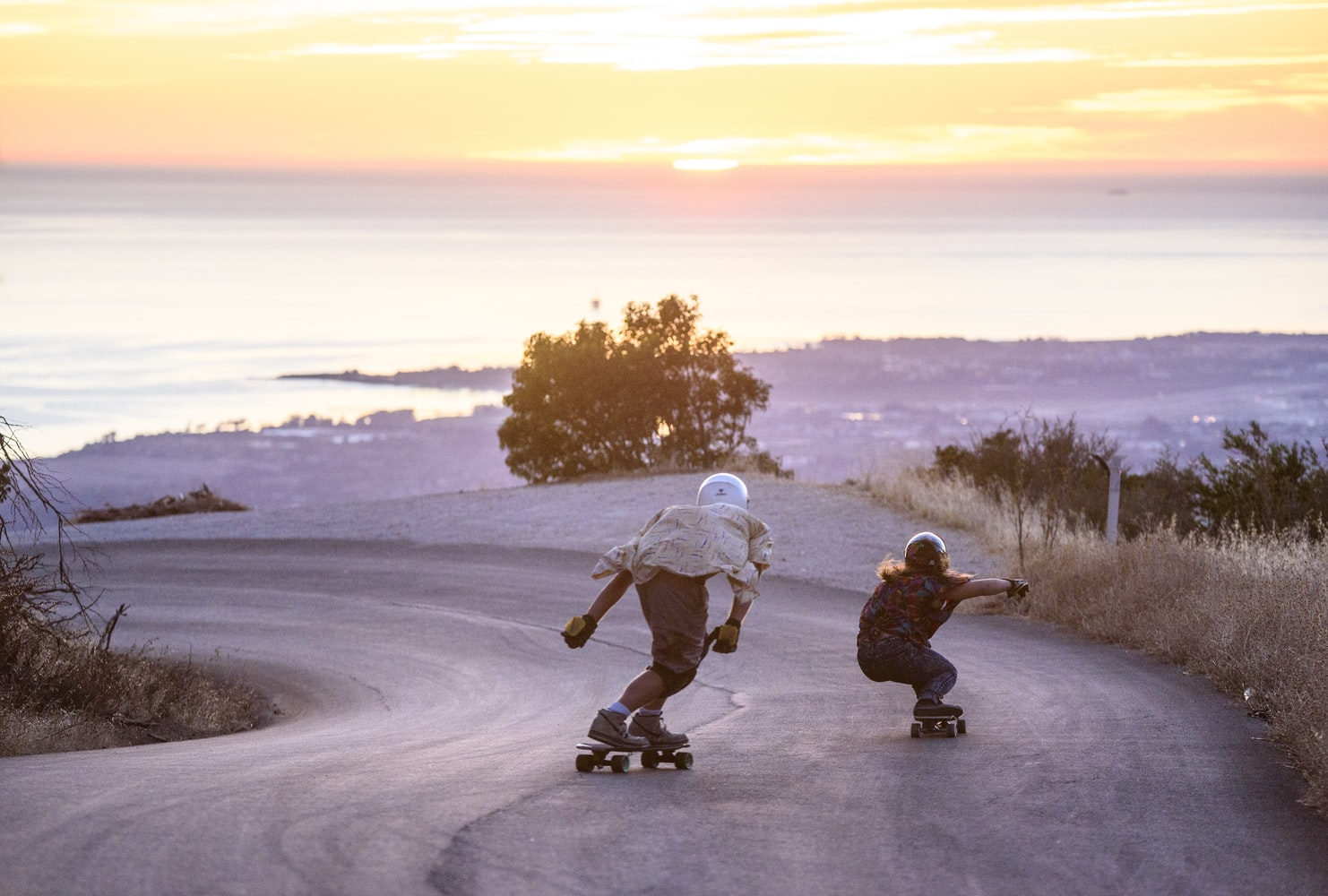 Two person wearing a helmet while riding a longboard during sunset