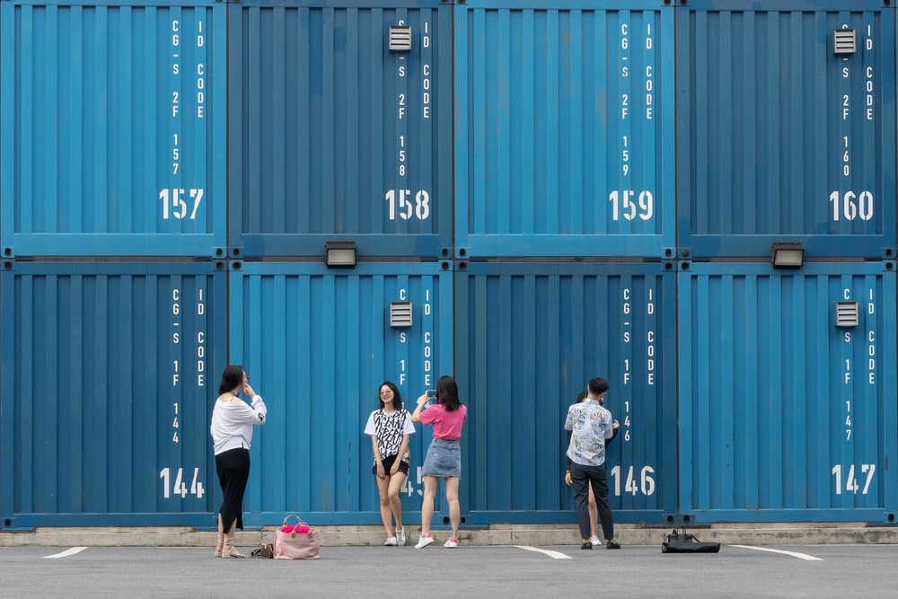 five women and man standing near shipping containers during daytime