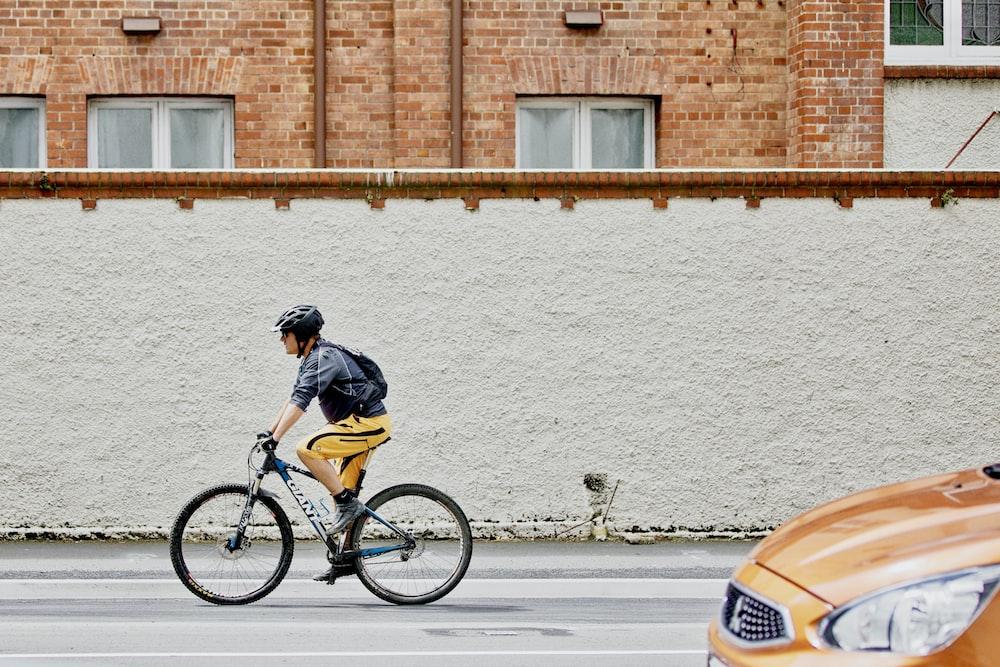 man riding black bike on street