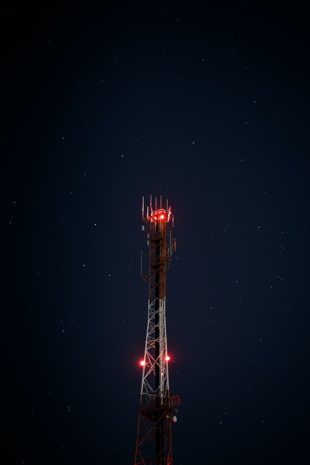 white and red metal satellite tower during nighttime