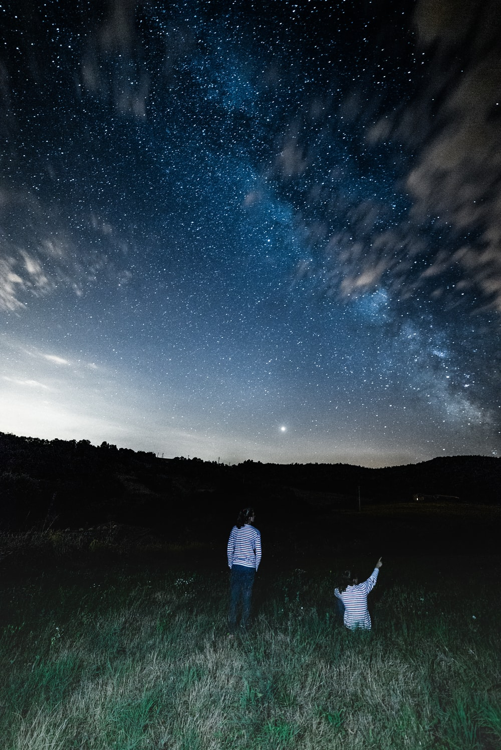2 people in white shirts in field watching star formations in night sky