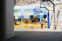 girl standing near basketball hoop and boat mural