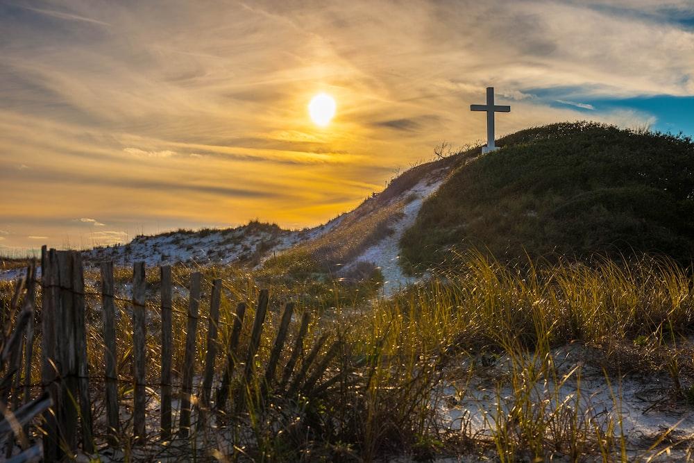 white cross on grass covered hilltop during sunrise