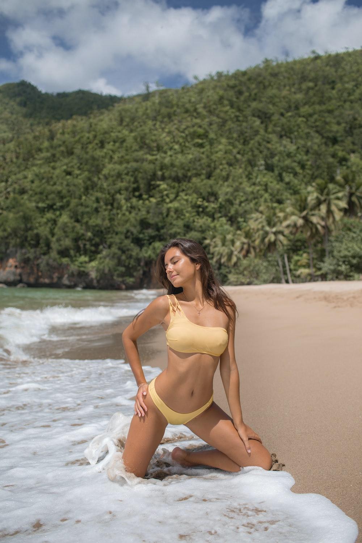 woman in yellow bikini kneeling on seashore