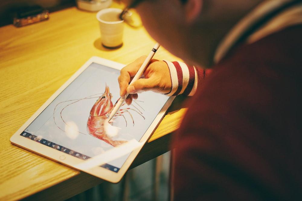 person draw shrimp on iPad