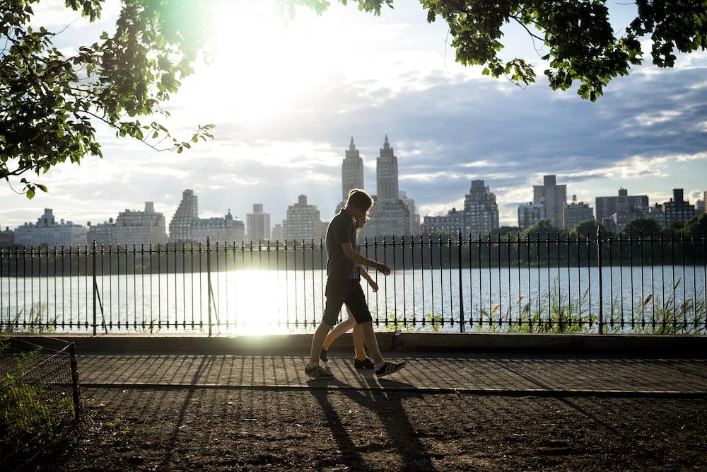 two persons walking beside fence beside body of water