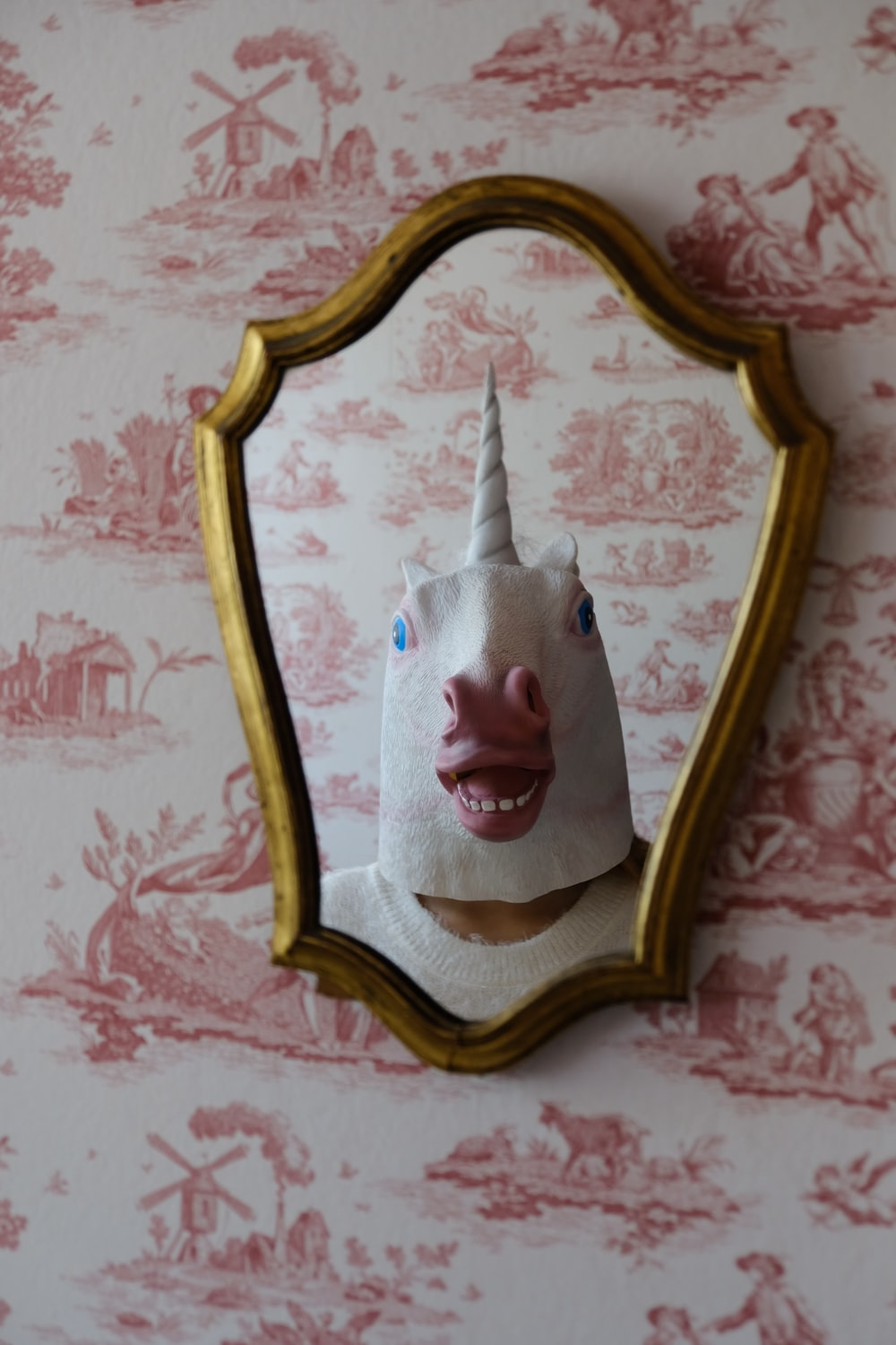 person with white unicorn mask stands in front of wall mirror