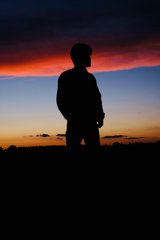 man standing under golden hour silhouette