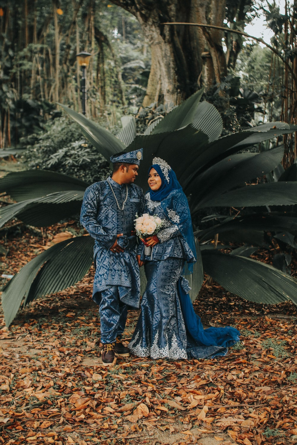 couple wearing matching thobe and dress in front of green plant during daytime