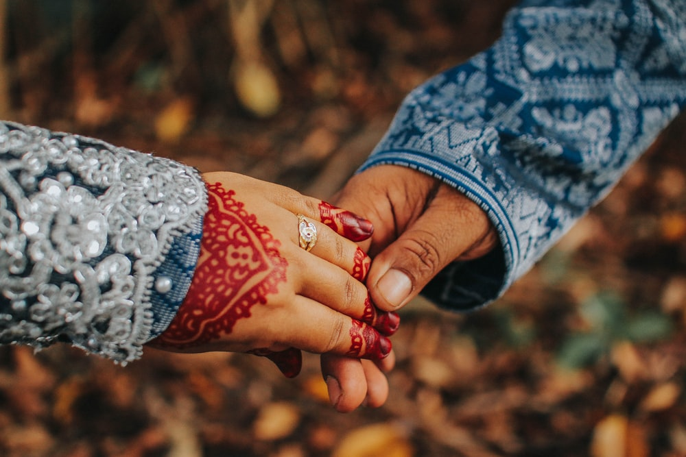 selective focus photography of man and woman holding hands