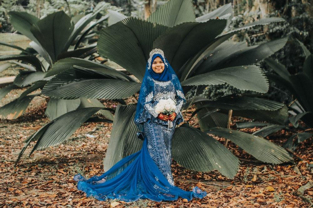 woman wearing blue floral dress standing beside plant