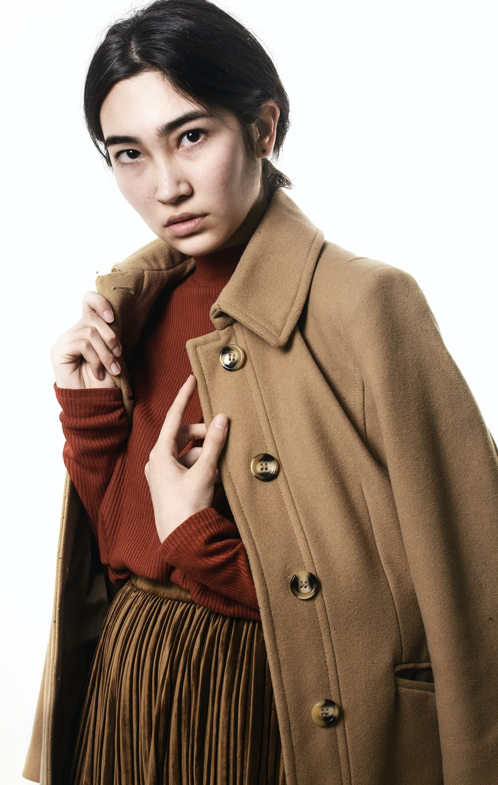 standing woman wearing maroon sweater and brown coat