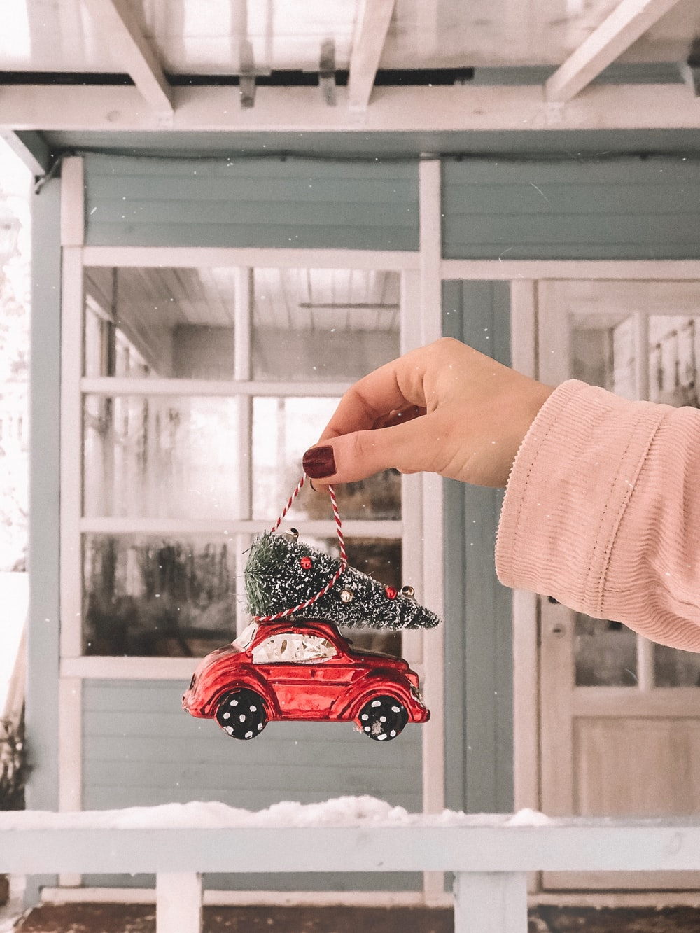 person holding red vehicle toy hanging decor