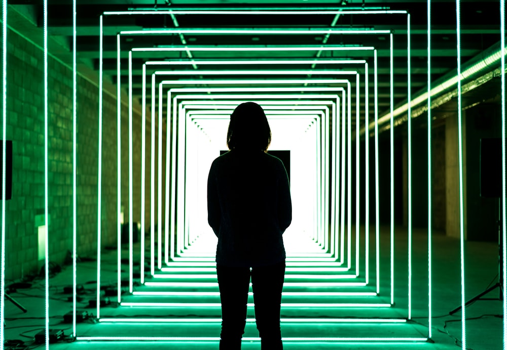 silhouette of woman standing in middle of green neon lighted cage