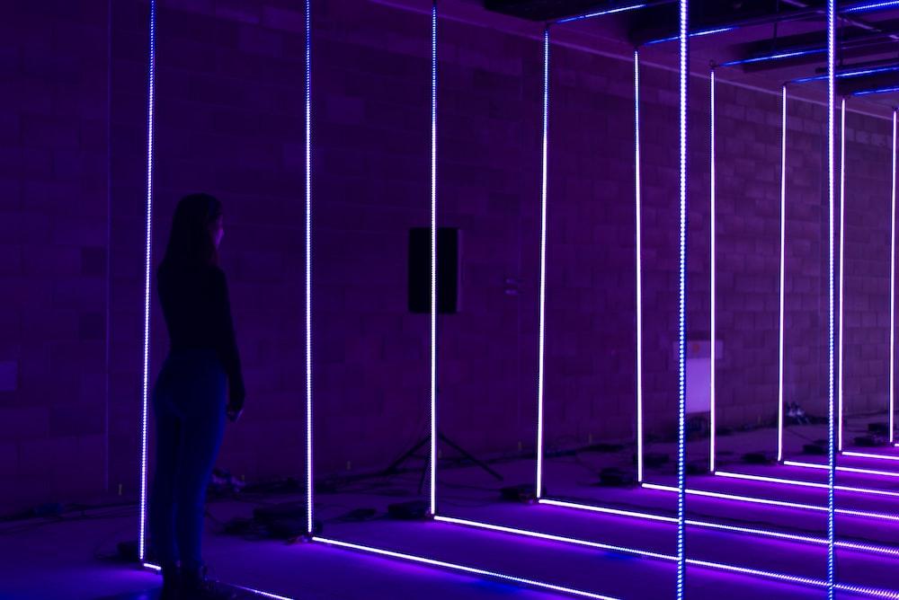 woman standing on purple led light string