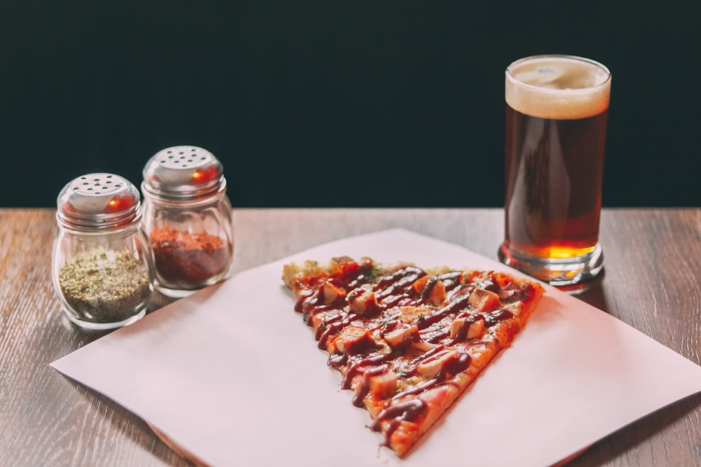 baked pizza beside two clear glass condiment shakers