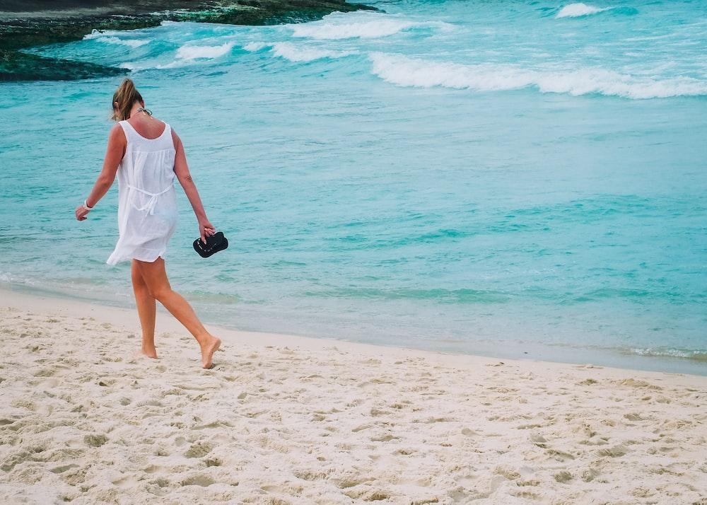 woman in white dress walks on white sand beach