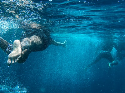 two person swimming in sea swimming teams background
