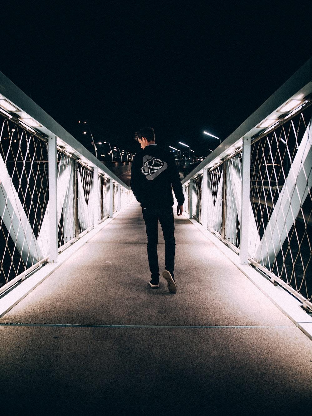 man walking on concrete bridge during nighttime