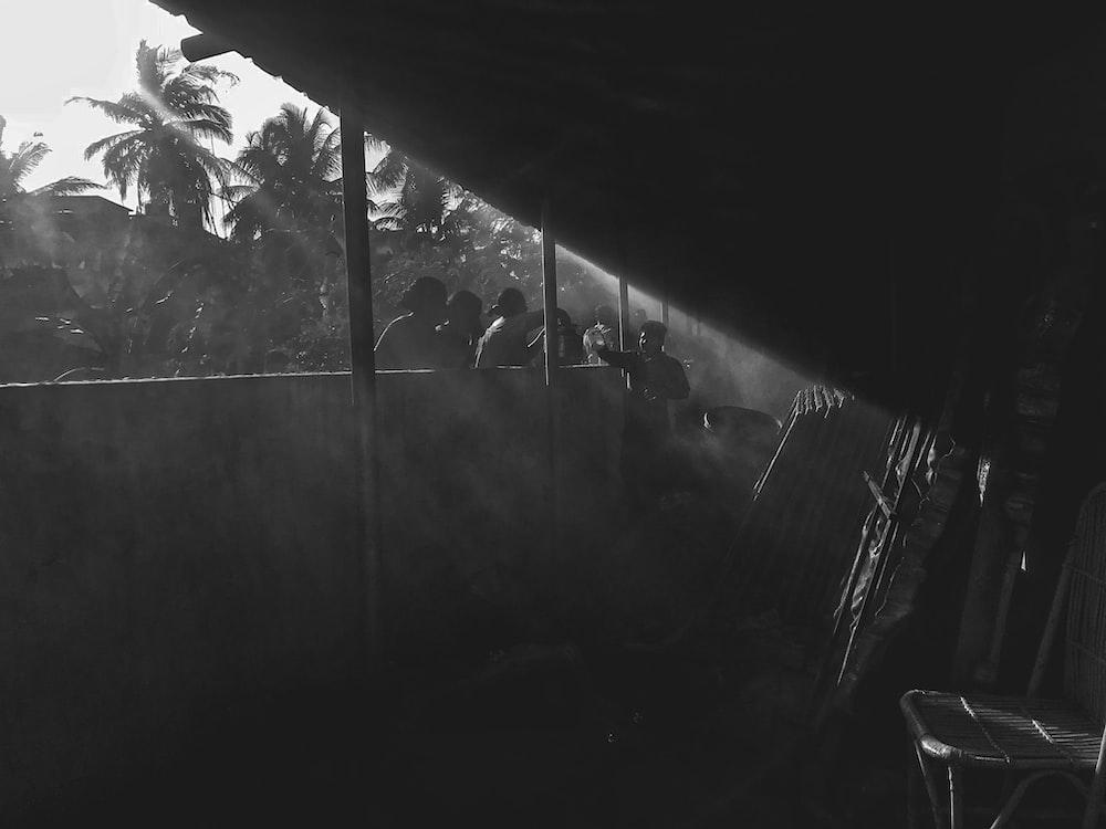 greyscale photo of people outside house