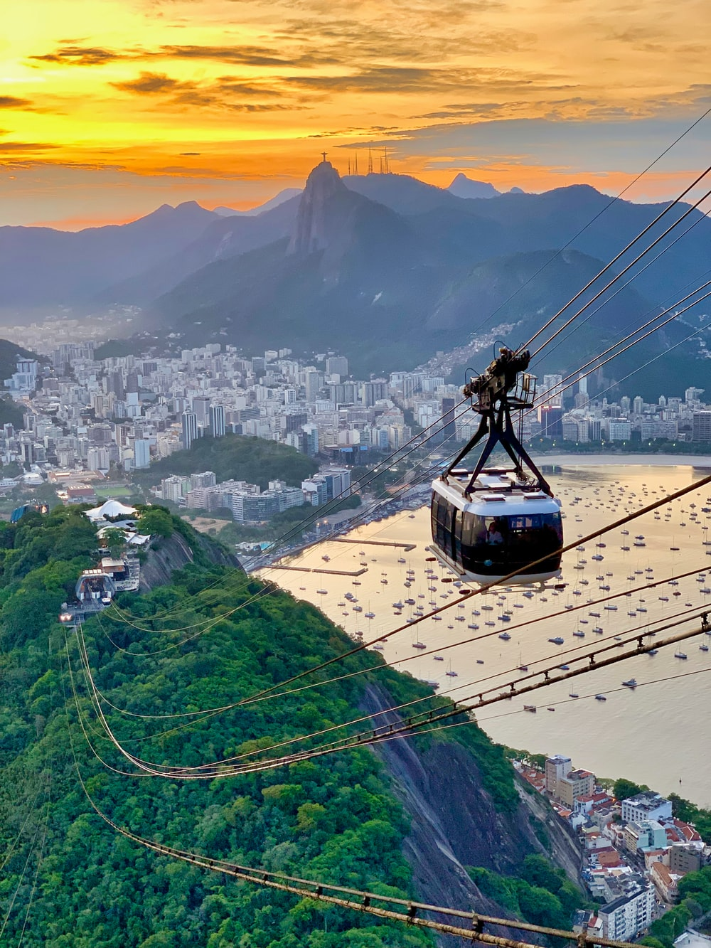 white cable car traversing on top of hills overlooking city by bay