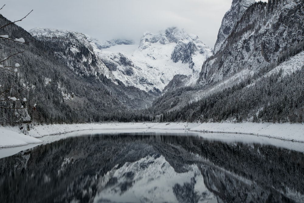 snow covered mountains near body of water during daytime