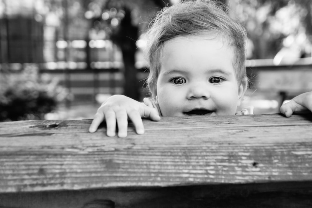 greyscale photo of baby on wooden bench