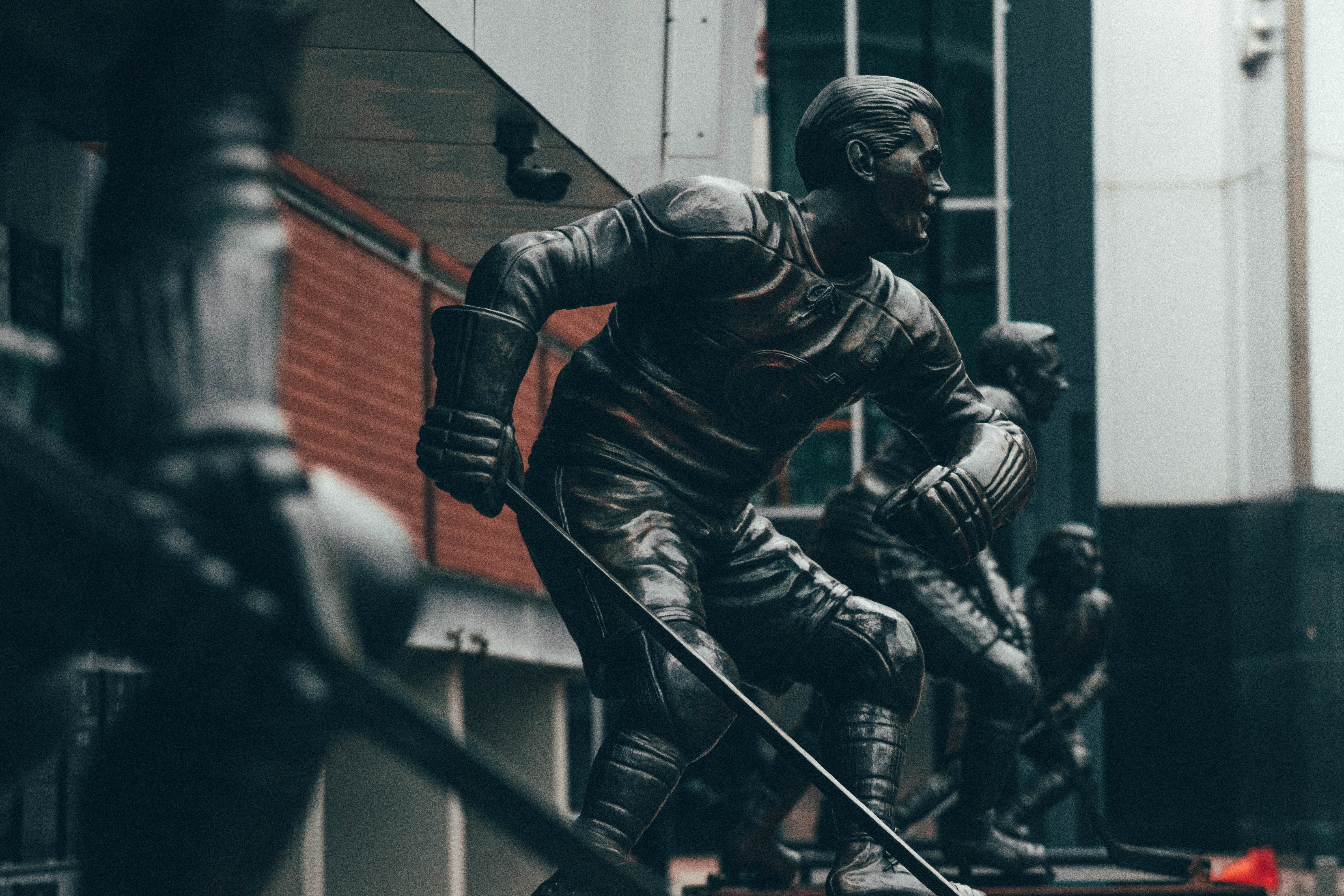 selective focus photography of ice hockey player statues
