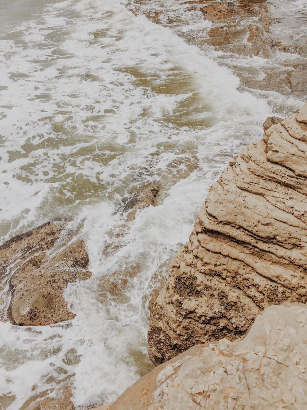 body of water beside rock formation