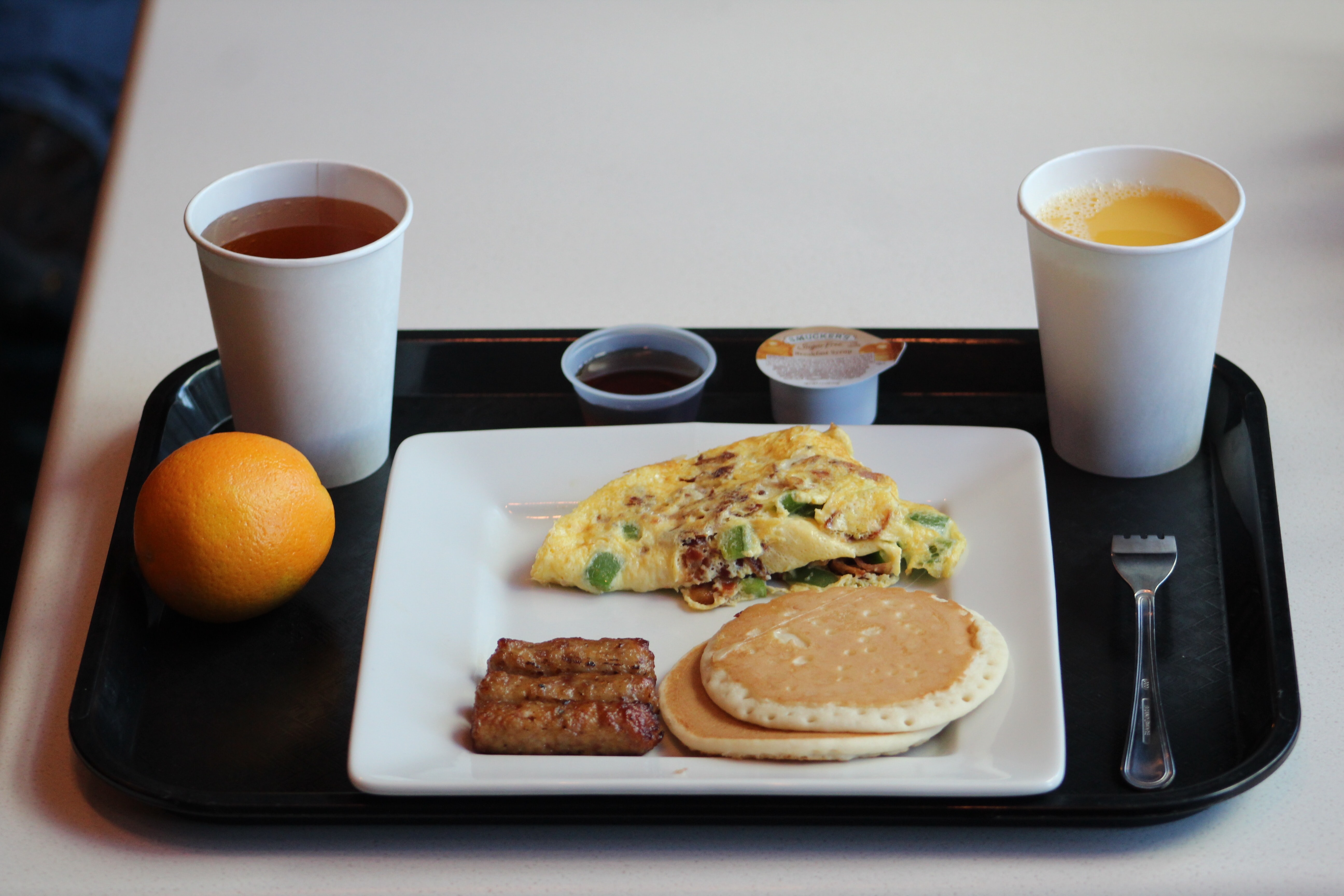 egg omelet with sausage, pancake and coffee on tray