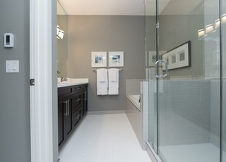 opened glass doors; black and white wooden cabinet with sink and two white towels on rack
