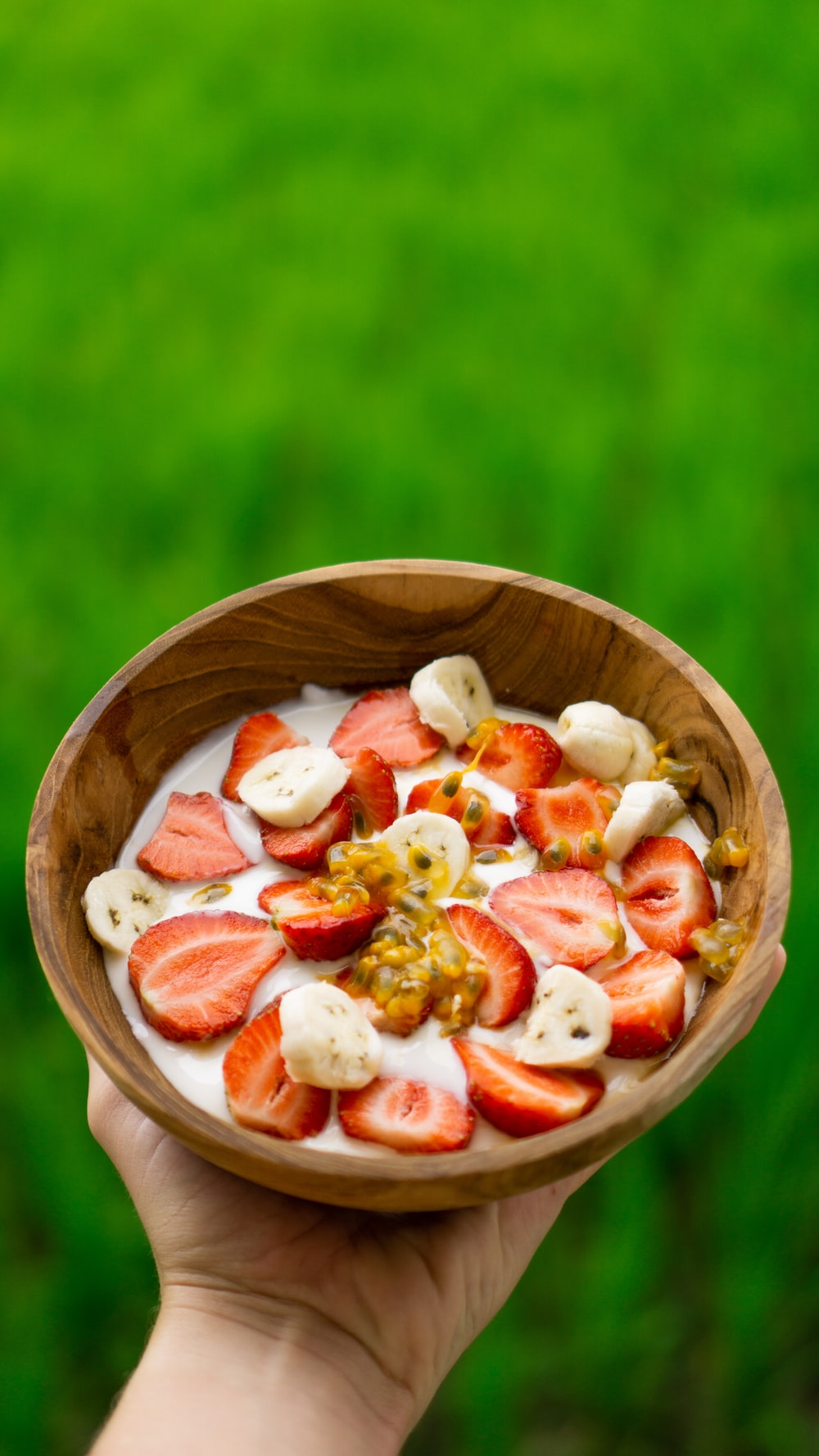 round brown wooden bowl with sliced strawberries