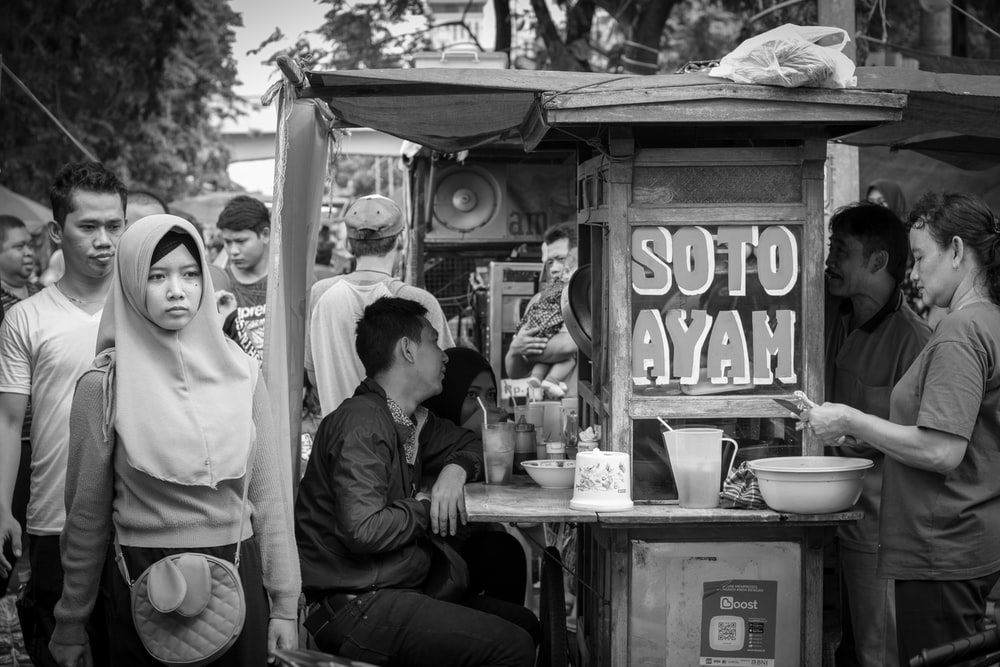 grayscale photography of people standing near booth