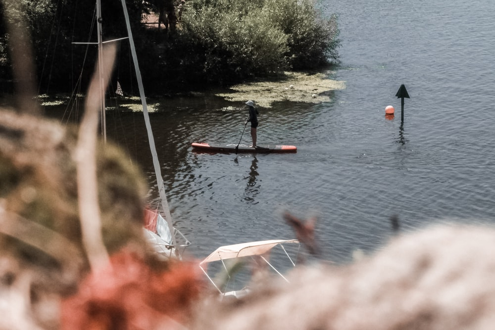 person with kayak on body of water during daytime