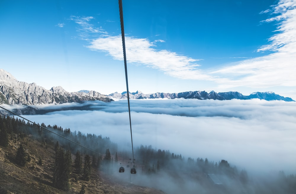 aerial photography of trees and mountains surrounded by fog