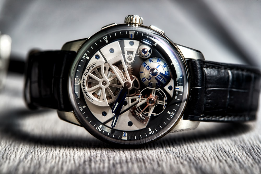 round silver-colored skeleton watch with black leather strap