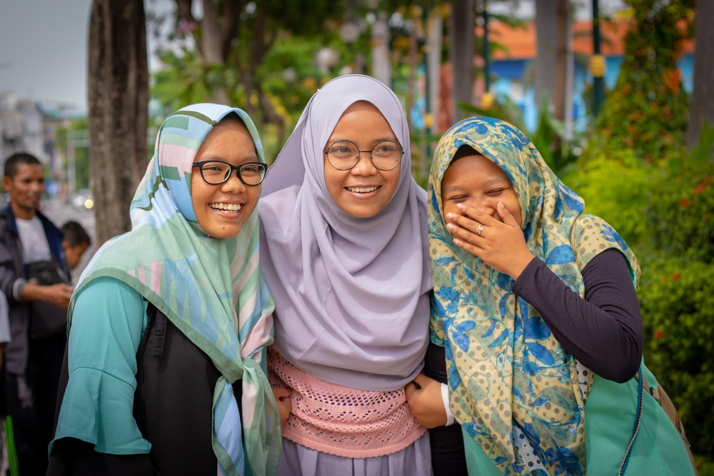 shallow focus photo of three girls wearing hijab headdress
